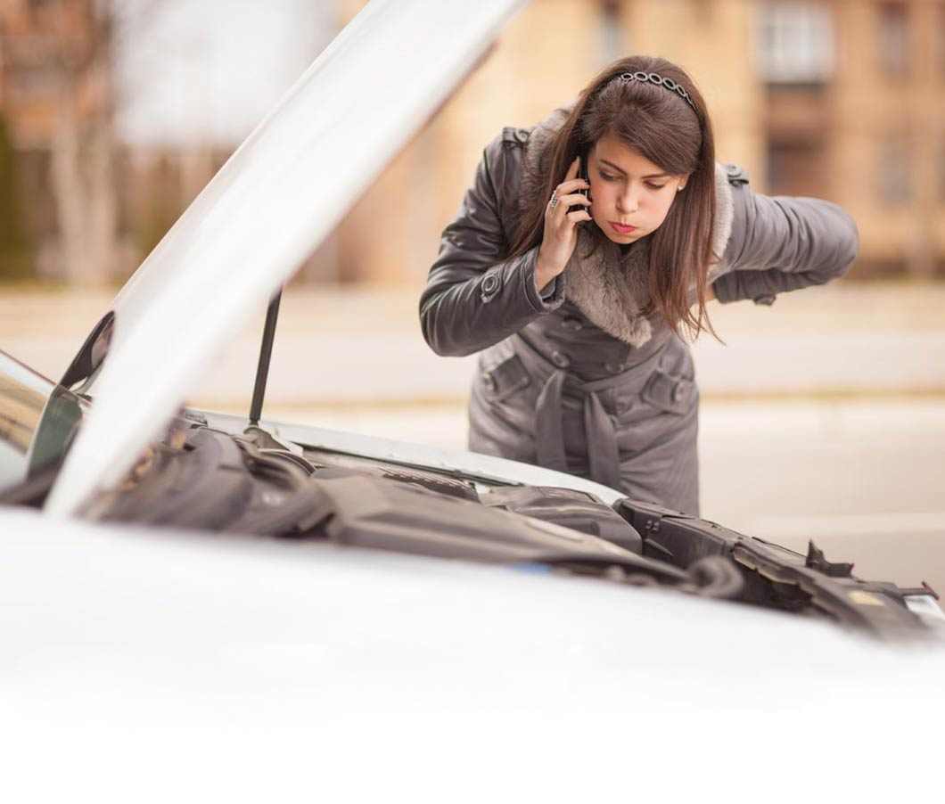 woman looking under hood of car waiting for roadside assistance
