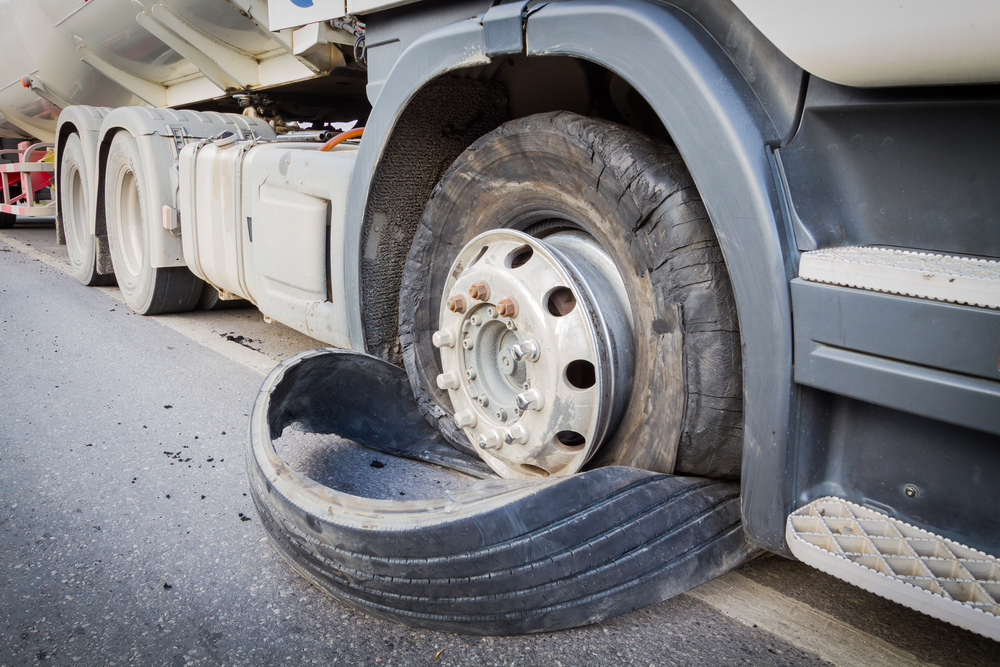 closeup damaged 18 wheeler semi truck burst tires by highway street