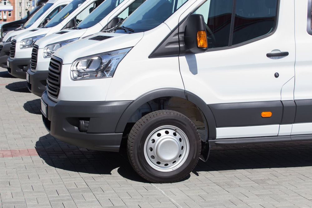 number of new white minibuses and vans outside
