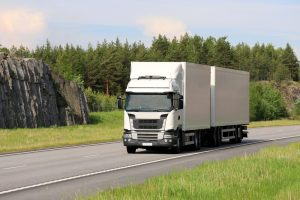 Landscape of motorway with big white cargo truck transporting goods at speed on a beautiful day of summer.