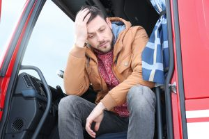 Sad or tired driver in cabin of big modern truck