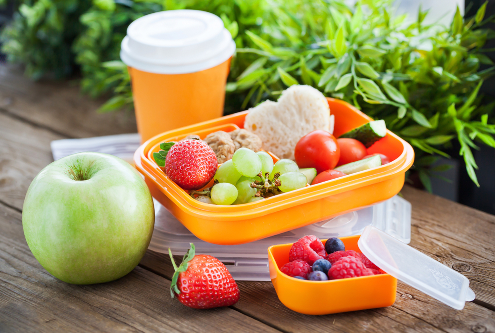 Lunch box for kids with sandwich, cookies, fresh veggies and fruits