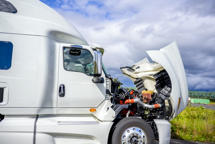 Broken Big rig industrial professional white semi truck with open hood and long haul semi trailer standing on the road shoulder trying to fix breakdown in place and waiting for road repair assistant