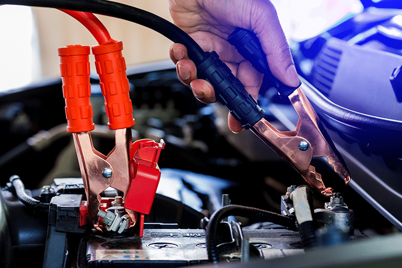 car battery with jumper cables attached
